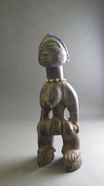 Yorùbá artist. <em>Female twin figure (Ère Ìbejì)</em>, 20th century. Wood, pigment, glass, 9 3/8 in. (23.8 cm). Brooklyn Museum, Gift of David R. Markin, 70.12.11. Creative Commons-BY (Photo: Brooklyn Museum, CUR.70.12.11_overall.jpg)