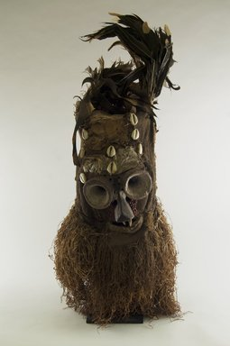 Luntu. <em>Fiber Mask with Conical Eyes (Batwape)</em>, late 19th or early 20th century. Burlap, wood, hide, cotton fiber, feathers, seeds, cowrie shells, pigment, 28 1/2 x 11 x 12 in. (72.4 x 28.0 x 30.5 cm). Brooklyn Museum, Gift of Marcia and John Friede, 74.121.3. Creative Commons-BY (Photo: Brooklyn Museum, CUR.74.121.3_front_PS5.jpg)