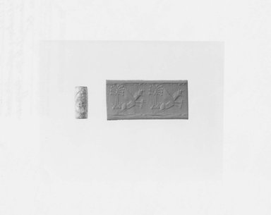 Ancient Near Eastern. <em>Cylinder Seal Depicting a Leaping Lion-Griffin and a Stylized Palm Tree</em>, 730-600 B.C.E. Chalcedony, 13/16 x Diam. 5/16 in. (2.1 x 0.9 cm). Brooklyn Museum, Gift of Dr. Martin Cherkasky, 78.113.1. Creative Commons-BY (Photo: Brooklyn Museum, CUR.78.113.1_NegA_print_bw.jpg)