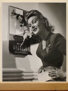 Philippe Halsman (American, born Latvia, 1906-1979). <em>[Untitled]  (Woman Pointing at Calendar, Holding Envelope in Other Hand; Smiling)</em>. Gelatin silver photograph Brooklyn Museum, Gift of Dr. and Mrs. Arthur E. Kahn, 85.294.16. © artist or artist's estate (Photo: Brooklyn Museum, CUR.85.294.16.jpg)