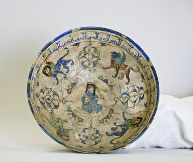 <em>Bowl Depicting a Seated Figure Surrounded by Winged Lions and Sphinxes</em>, late 12th-early 13th century. Ceramic, mina'i (enameled) or haft rangi (seven-colors) ware; fritware, in-glaze painted in blue, green, and brown on an opaque white glaze, overglaze painted in black, 3 1/4 x 7 in. (8.3 x 17.8 cm). Brooklyn Museum, Gift of the Ernest Erickson Foundation, Inc., 86.227.63. Creative Commons-BY (Photo: Brooklyn Museum, CUR.86.227.63_interior.jpg)