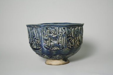 Hasan Al-Qashani. <em>Octagonal Bowl with Inscriptions</em>, late 12th century. Ceramic; fritware, with carved and molded decoration under a cobalt blue glaze, 4 5/16 x 6 3/8 in. (11 x 16.2 cm). Brooklyn Museum, Gift of the Ernest Erickson Foundation, Inc., 86.227.89. Creative Commons-BY (Photo: Brooklyn Museum, CUR.86.227.89_view1.jpg)