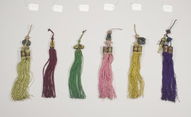 <em>Tassel (Norigae) with Boy Figure Decorations</em>, 20th century. Enameled silver, metallic thread, string, 11 7/16 x 1 1/16 in. (29 x 2.7 cm). Brooklyn Museum, Brooklyn Museum Collection, X1161. Creative Commons-BY (Photo: , CUR.X1163_X1162_X1160_X1161_X1159_X1164_Collins_photo_NRICH.jpg)