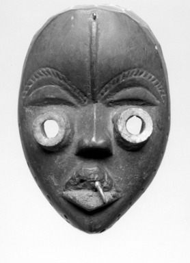 Dan. <em>Mask</em>, late 19th or early 20th century. Wood, metal, tooth, plastic?, 8 x 5 1/2 x 4in. (20.3 x 14 x 10.2cm). Brooklyn Museum, Brooklyn Museum Collection, X956.5. Creative Commons-BY (Photo: Brooklyn Museum, CUR.X956.5_bw.jpg)