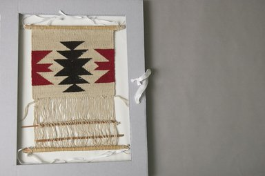 Navajo. <em>Model of Loom, Including Frame, Warp, Shed Rod and a Hed Rod with Partially Woven Blanket</em>, early 20th century. Wood, wool, loom: 15 1/2 x 10 in. Brooklyn Museum, Brooklyn Museum Collection, X698a-d. Creative Commons-BY (Photo: Brooklyn Museum, X698a-d_PS5.jpg)
