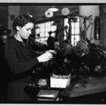 [Untitled]  (Young Woman Standing at Tabletop Thread Machine)