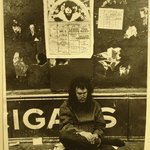 [Untitled] (Man sitting on street beneath 1969 Brooklyn Academy of Music poster, New York)