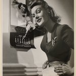 [Untitled]  (Woman Pointing at Calendar, Holding Envelope in Other Hand; Smiling)