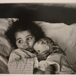 [Untitled] (Juanita Lying in Bed Hugging Doll)
