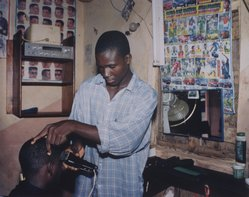 Timothy Feresten (American, born 1954). <em>Haircut, Local Market (Ebonyi State, Nigeria, July 2000)</em>, 2001. Dye coupler print, Sheet: 20 x 24 in. (50.8 x 61 cm). Brooklyn Museum, Gift of the artist, 2002.111.2. © artist or artist's estate (Photo: Brooklyn Museum, 2002.111.2.jpg)