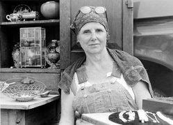 Angelo Dounoucos (American, born 1932). <em>[Untitled] (Seated Woman in Overalls Selling Antiques)</em>, 2002. Gelatin silver photograph, Sheet: 16 x 19 7/8 in. (40.6 x 50.5 cm). Brooklyn Museum, Gift of the artist, 2002.77.2. © artist or artist's estate (Photo: Brooklyn Museum, 2002.77.2_bw.jpg)