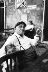 Mary Ellen Mark (American, 1940-2015). <em>Old Man with Suspenders Smoking + Girl Behind Chair, Italy</em>, 1965; printed ca. 1965. Gelatin silver photograph, Sheet: 14 × 10 15/16 in. (35.6 × 27.8 cm). Brooklyn Museum, Gift of Howard Greenberg, 2019.50.14. © artist or artist's estate (Photo: Image courtesy of the estate of Mary Ellen Mark, CUR.2019.50.14_MaryEllenMarkEstate_photograph.jpg)