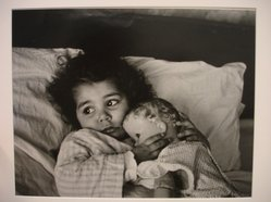 W. Eugene Smith (American, 1918-1978). <em>[Untitled] (Juanita Lying in Bed Hugging Doll)</em>, n.d. Gelatin silver photograph, Sheet: 9 3/4 x 11 5/16 in. (24.8 x 28.8 cm). Brooklyn Museum, Gift of Philip Goutell, 87.245.13. © artist or artist's estate (Photo: Brooklyn Museum, CUR.87.245.13.jpg)